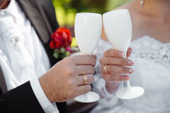 Hands of the bride and groom with white glass rings stock image