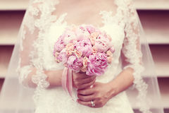 Hands of a bride holding peonies bouquet Royalty Free Stock Photography