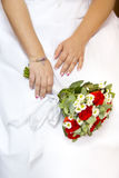 Hands of bride holding wedding bouquet of red and white flowers Royalty Free Stock Photos
