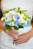 Hands of bride holding wedding bouquet of white and blue flowers. Hands of bride in lace wedding dress holding wedding bouquet of white and blue flowers stock photo