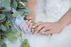 Hands of a bride, just married, a bridal bouquet is beside Stock Photo