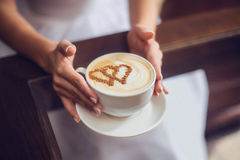 Hands of bride with latte art coffee cup Stock Photo