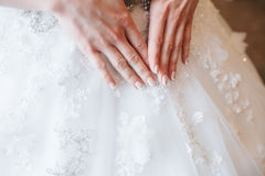 Hands bride with manicure on background of white dress. Hands bride with a manicure on the background of white lace dress Royalty Free Stock Images