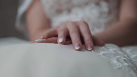 Hands of the bride on the wedding dress. Close up. Nice manicure stock footage