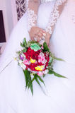 Hands of the bride in a white dress with a bouquet of red roses Royalty Free Stock Image