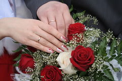 Hands of the bridegroom and bride. On background of the bouquet royalty free stock photos