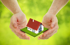 Hands brings small house Stock Images