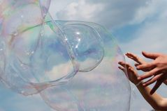 Hands and Bubbles against the sky Stock Images