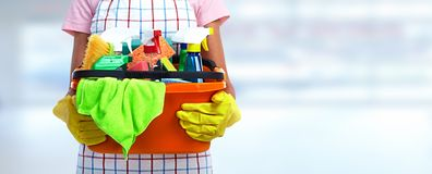 Hands with bucket of cleaning products. stock photography