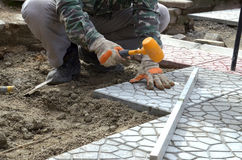 Hands of a builder laying new paving stones carefully placing on Royalty Free Stock Images