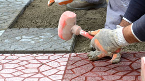 Hands of a builder laying new paving stones carefully placing one in position on a leveled and raked sand base Royalty Free Stock Photo