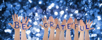 Hands Building Word Be Grateful, Glittering And Sparkling Bokeh Background. Many Hands Building English Word Be Grateful. Glittering, Sparkling And Magic Bokeh stock photo