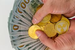 Hands with bundle of banknotes with coins. Hands holding bundle of dollars with golden coins Royalty Free Stock Image