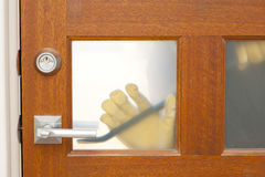 Thief housebreaking security door crowbar. Hands of Burglar, thief  with gloves, holding crowbar trying to break in home, unlock door, blurred visible silhouette Stock Photography