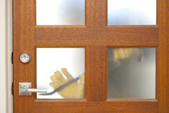 Burglar housebreaking security door. Hands of Burglar, thief  with gloves, holding crowbar trying to break in home, unlock door, blurred visible silhouette Stock Photo