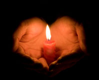 Hands and a burning candle Royalty Free Stock Images