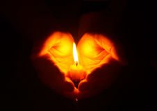 Hands and  burning candle in dark Royalty Free Stock Image
