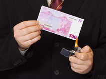 Hands and burnning money Stock Images