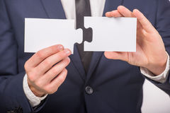 Hands. Business man holding pieces of puzzle on white background. Close-up Royalty Free Stock Photography