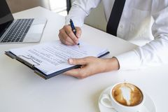 Hands of business man signing the contract document with pen on desk royalty free stock image