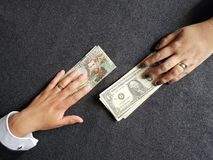 Hands of business man and woman exchanging colombian banknotes and american dollars bills. Backdrop for announcements of trading and exchange, bank and commerce stock image