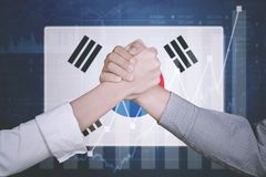 Handshake with South Korea flag. Hands of business partner shaking hands for deal cooperation growth chart and South Korea flag royalty free stock image