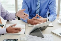 Brainstorming session. Hands of business people discussing report on tablet screen Royalty Free Stock Images