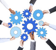 Hands of Business People Holding Gear Symbols Stock Image