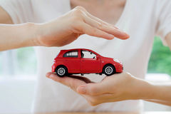Hands of a business woman holding a red toy car Royalty Free Stock Images