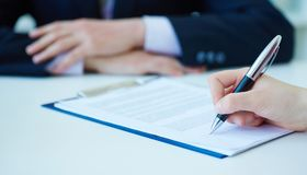 Hands of business woman signing the contract document with pen on desk. Selective focus image on sign a contract. Hands of business woman signing the contract Royalty Free Stock Photos