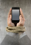 Hands of businessman addicted to mobile phone rope bond wrists in smartphone internet addiction Stock Photo