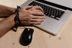 Hands of businessman addicted to work bond with mouse cable to computer laptop in workaholic Stock Photography