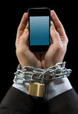 Hands of businessman addicted to work chain locked in mobile phone addiction stock photography