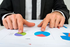 Hands of a businessman analysing two pie graphs Stock Photos