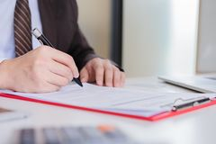 Hands of businessman brown suit are signing contract agreement. stock photos