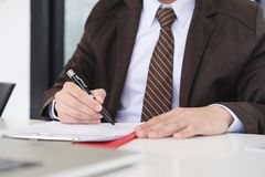 Hands of businessman brown suit are signing contract agreement. royalty free stock photography