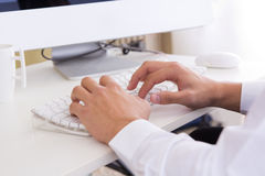 Hands of businessman with a computer keyboard. Detail of hands of businessman with a computer keyboard royalty free stock photo