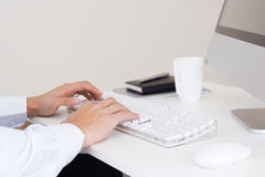 Hands of businessman with a computer keyboard. Detail of hands of businessman with a computer keyboard stock photo