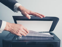 Hands of businessman copying document. The hands of a young businessman is placeing a document on a flatbed scanner in preperation for copying it royalty free stock photo
