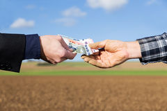 Hands of a businessman and farmer with a money transfer Royalty Free Stock Photos