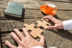 Hands of a businessman holding two jigsaw puzzle pieces Royalty Free Stock Photo