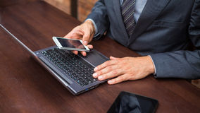 Hands of businessman with laptop and mobile phone. Stock Photo