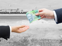 Hands of businessman passing Australian dollar (AUD) banknote. Stock Photography