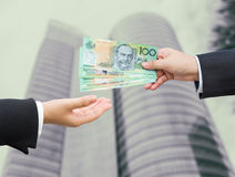 Hands of businessman passing Australian dollar (AUD) banknote. Royalty Free Stock Photography
