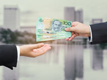 Hands of businessman passing Australian dollar (AUD) banknote. Royalty Free Stock Images
