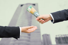 Hands of businessman passing Australian dollar (AUD) banknote wi Royalty Free Stock Photo