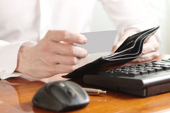 Hands of businessman with purse and bank card on the computer keyboard Stock Photography