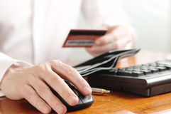 Hands of businessman with purse and bank card on the computer keyboard Stock Images