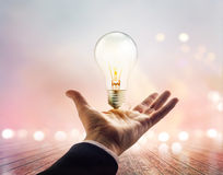 Hands of a businessman reaching to towards light bulb on wooden Royalty Free Stock Images