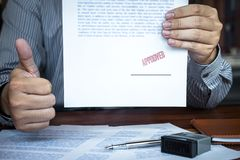 Hands of businessman stamp on paper document to approve business investment contract agreement stock photo